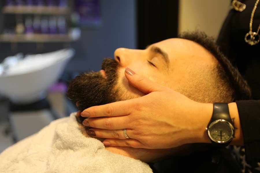 Barbier, client du salon les Essentielles recevant un soin de barbe à l'institut