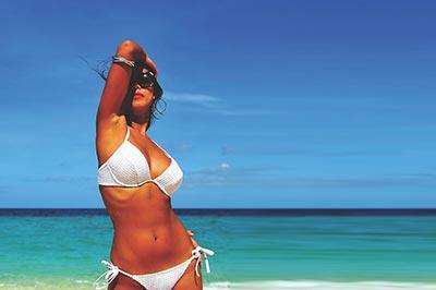 bronzage sans UV, femme en bikini blanc sur la plage