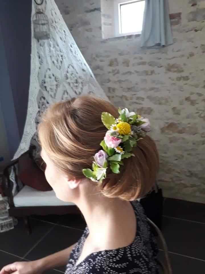 coiffure et maquillage pour mariage, chignon avec fleurs pour mariée d'une cliente assise au salon