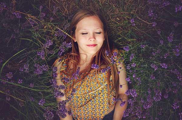 Femme souriante allongée dans un champ de lavande.