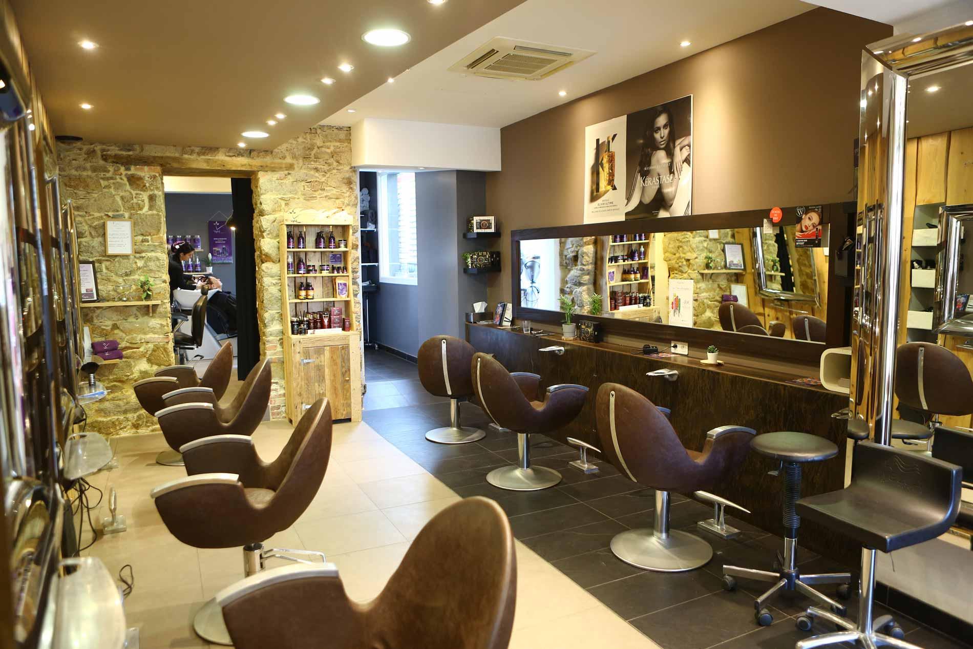 Salon de coiffure les essentielles, fauteuils et miroirs avec décoration en pierre sur les murs.