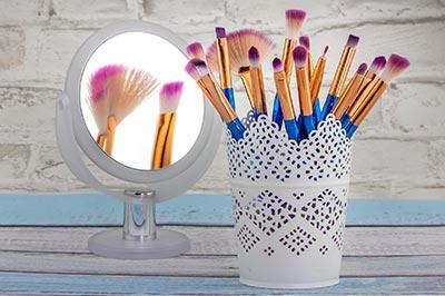 Maquillage femme, pot avec pinceaux de maquillage à coté d'un miroir