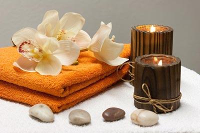 Institut de beauté pour femmes et hommes, bougie marron et serviette orange avec orchidées et pierres