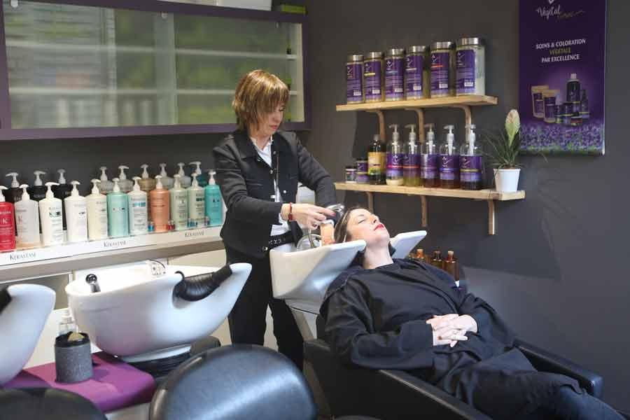 Salon de coiffure femmes, cliente au bac à shampoing avec coiffeuse