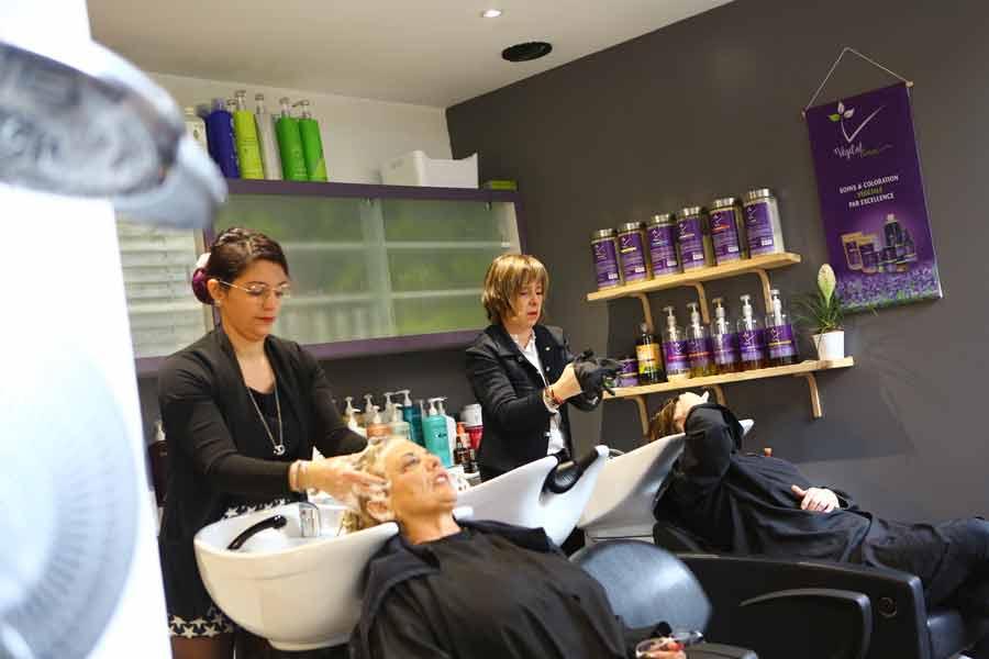 Salon de coiffure femmes, clientes au bac à shampoing avec coiffeuses