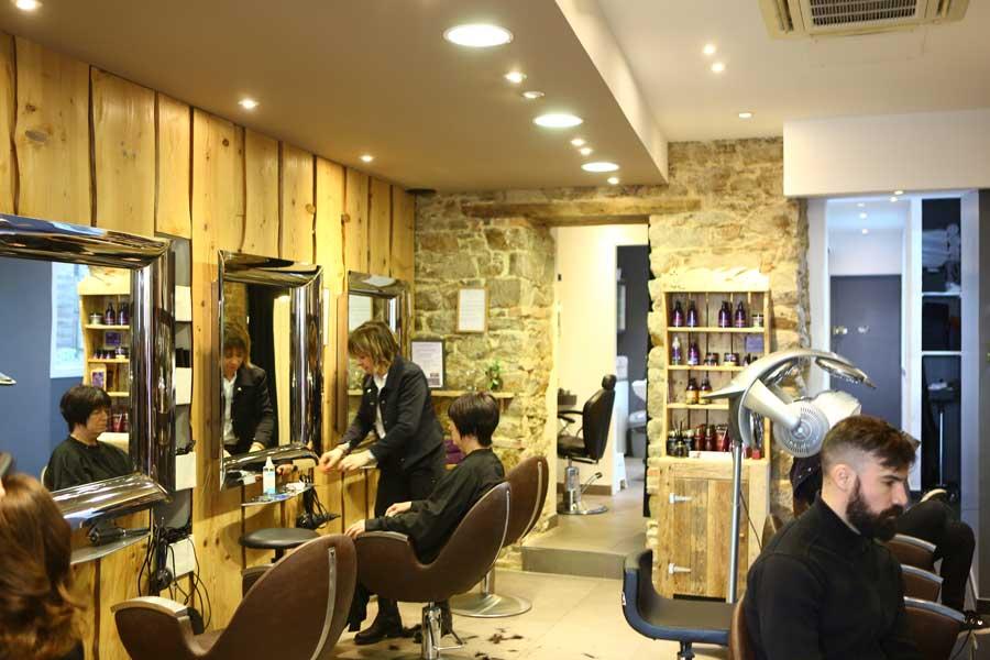 Salon de coiffure hommes, clients assis face miroirs avec coiffeuse.