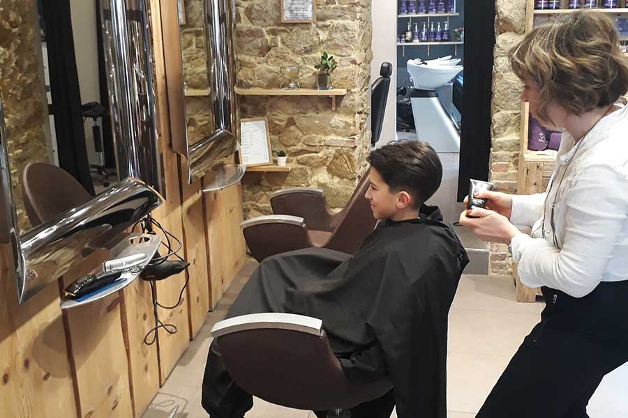 Salon de coiffure, enfant assis face miroir avec coiffeuse.