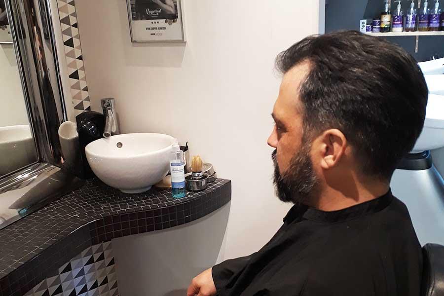 Salon de coiffure, client assis devant miroir avec barbe