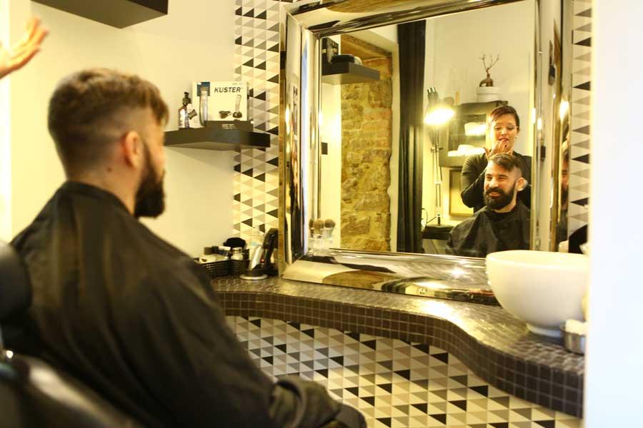 Salon de coiffure hommes, client assis face miroir avec coiffeuse.