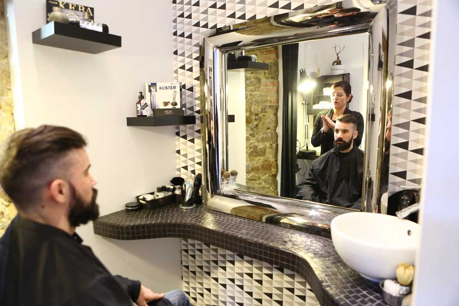 Salon de coiffure, client assis face miroir avec coiffeuse