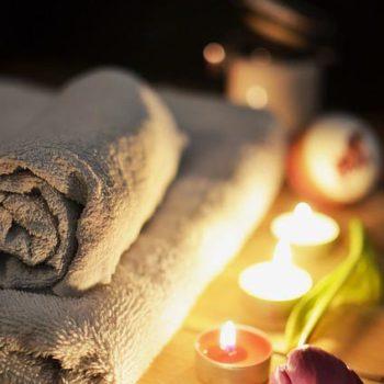 Soins du visage pour femme, bougies avec rose et serviette pliée.