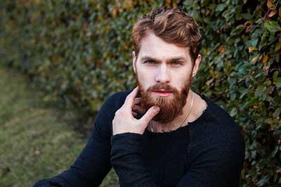 Coupe homme au salon les essentielles. Homme avec barbe et coiffure moderne.